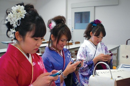 Japanese women using smartphones and a camera