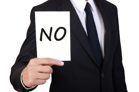 Businessman holding 'No' card
