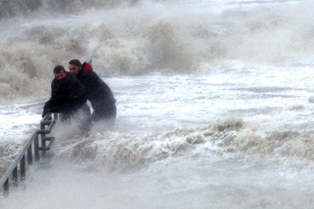 Men clinging to railings among strong waves