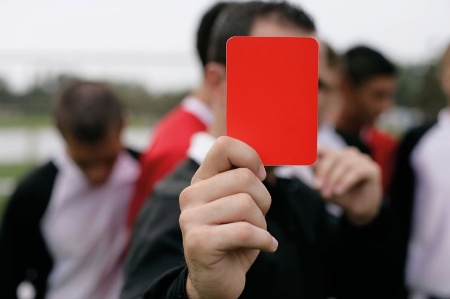 Man holding soccer red card