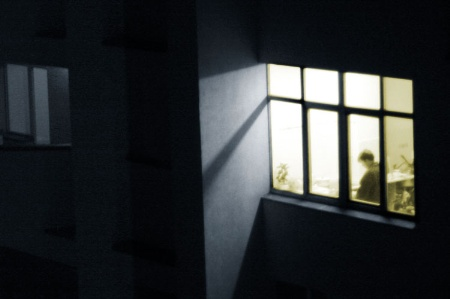 Person viewed through window, working late in office