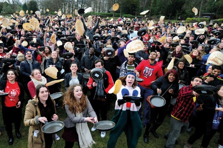 Crowd of students flipping pancakes