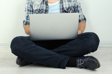 Seated man working on laptop