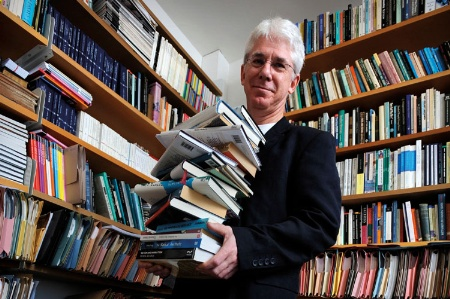 Thomas Docherty holding pile of books