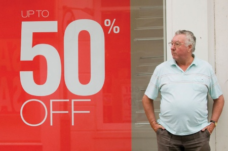 Man standing next to '50% off' sign in shop window