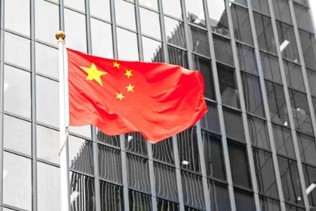 Chinese flag flying outside corporate building