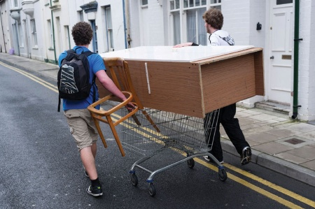 Male students moving furniture on shopping trolley