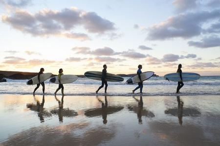 Surfers on beach carrying surfboards