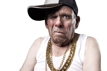 Old man wearing baseball cap and gold chains