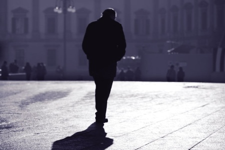 Man walking on pavement at dusk