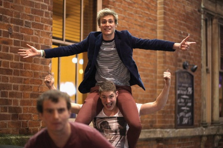 Male student sitting on friend's shoulders