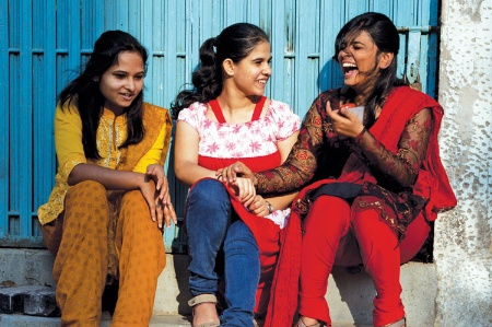 Three young women seated, chatting and laughing