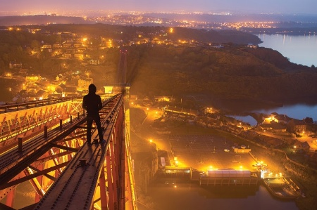 Young man walking along suspension bridge at night