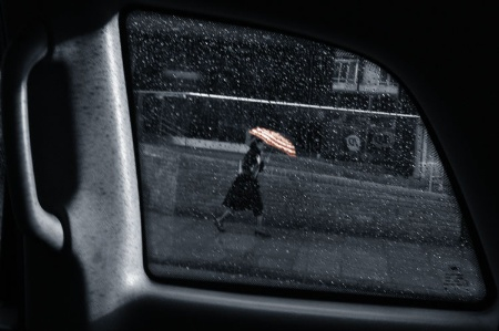 Woman walking in rain with umbrella, viewed through taxi window