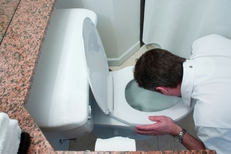 Man looking into toilet bowl