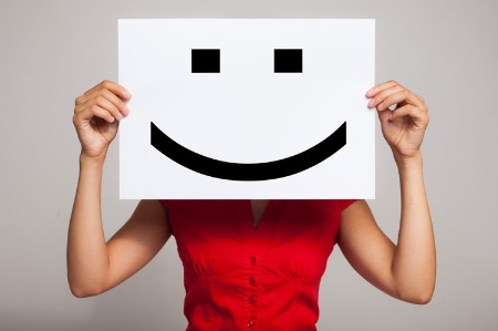 Woman holding smiley emoticon sign