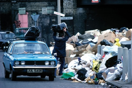 Man throwing rubbish bag onto a pile