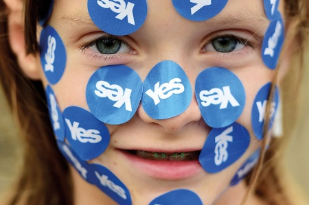 A girl wearing yes stickers on her face