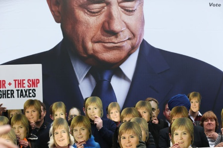 People wearing Nicola Sturgeon face masks in front of a large poster of Alex Salmond