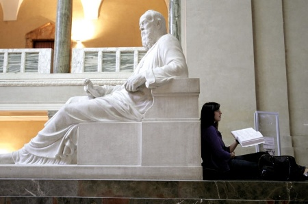 Female student leaning against statue