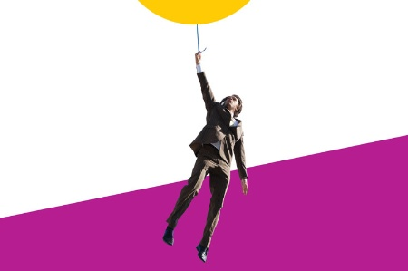 Businessman hanging from balloon