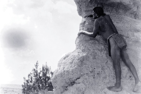 Native American man climbing rocks
