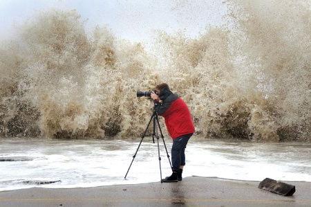 Man taking picture of crashing wave