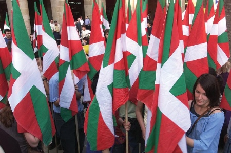 Woman standing amongst Basque flags