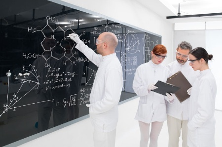 Four scientists working by blackboard