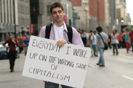 Anti-capitalism demonstrator holding sign