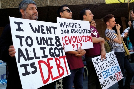 Demonstrators holding student debt signs