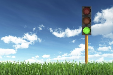 Green traffic light on grass