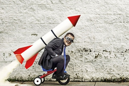 Man sitting on rocket-propelled tricycle