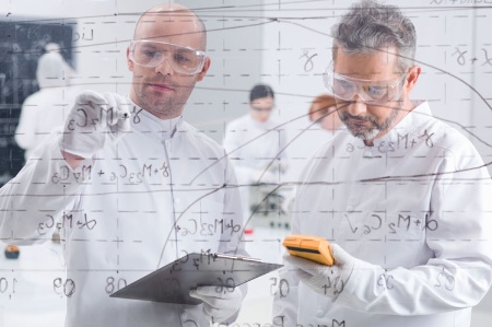 Two scientists writing formulae