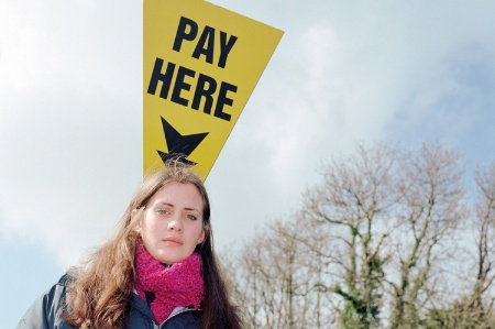 Woman standing underneath 'Pay here' sign