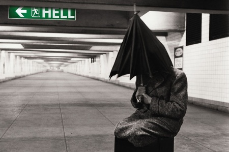 Man hiding beneath umbrella next to 'Hell' sign