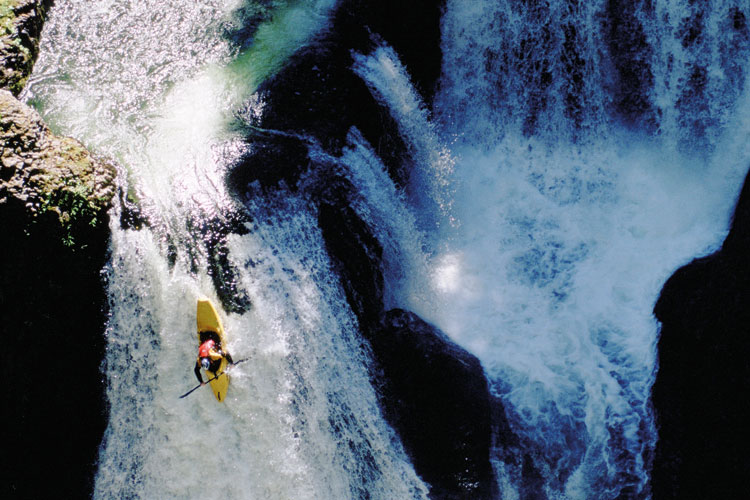 A person taking a canoe down a waterfall