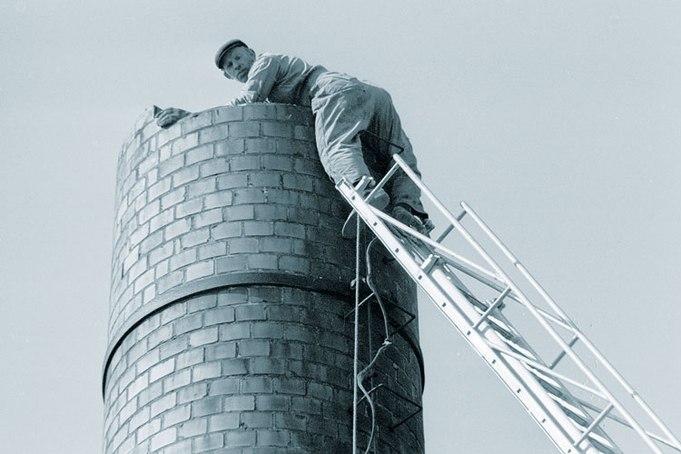 A man standing on a ladder at the top of a chimney