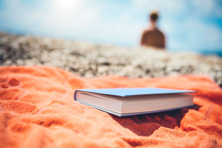 Book on towel on beach