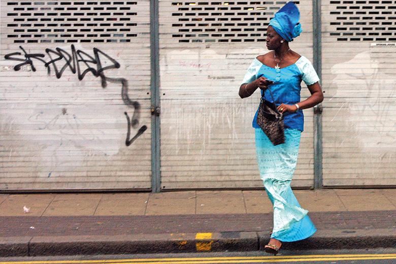 Brightly dressed woman crossing street, Peckham, London