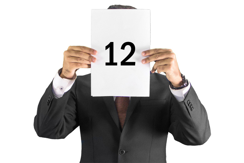 Businessman holding number twelve (12) scorecard