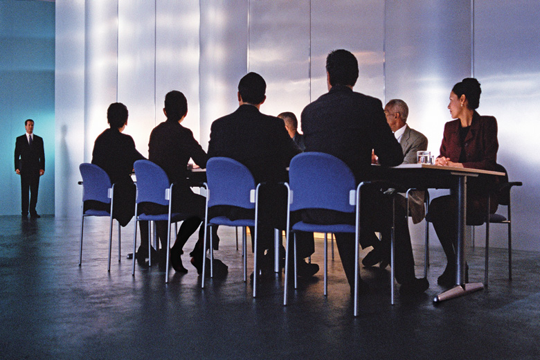 Businessman standing before table of executives