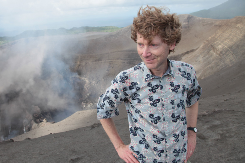 Clive Oppenheimer posing beside smoking volcano