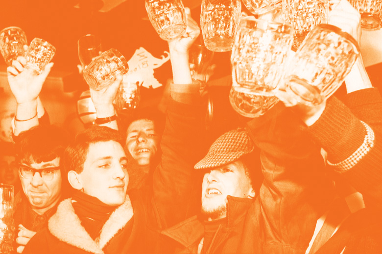 Crowd of men raising pint glasses in pub