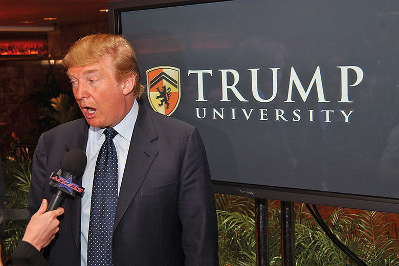 Donald Trump next to Trump University sign