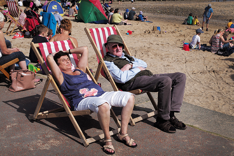 Elderly British couple in deckchairs at the seaside