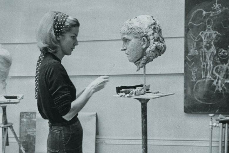 Female artist working on bust head sculpture