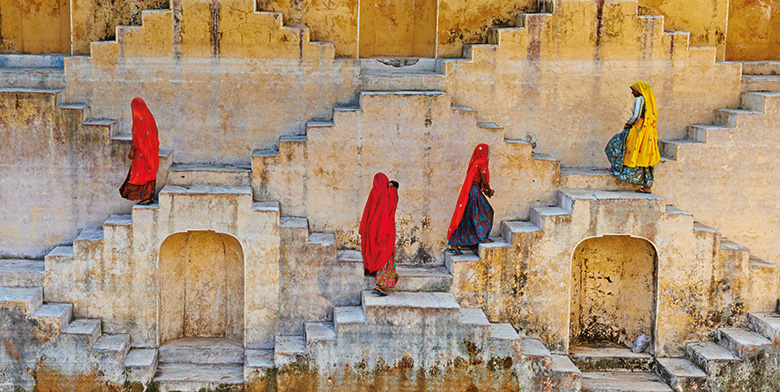 Four Indian women walking up and down staircases