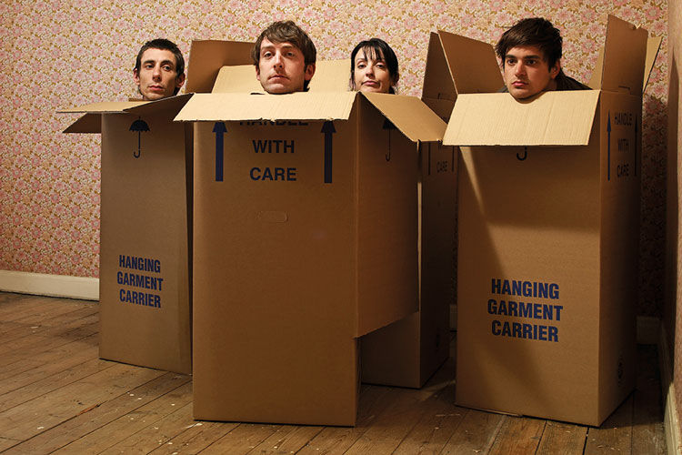 Four people sitting in cardboard boxes