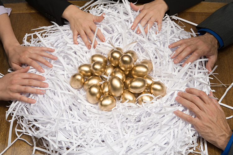 Colleagues around a nest of gold eggs